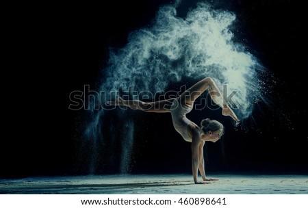Graceful woman dancing in cloud of dust
