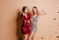 Graceful woman with shy smile looking away, holding goblet of good champagne. Indoor portrait of two smiling european girls relaxing at new year party.