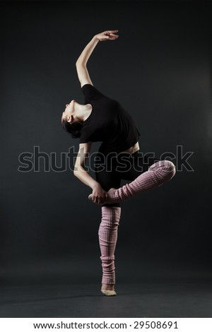 graceful young woman against dark background