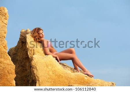 Graceful young woman in bikini lying on the yellow rock