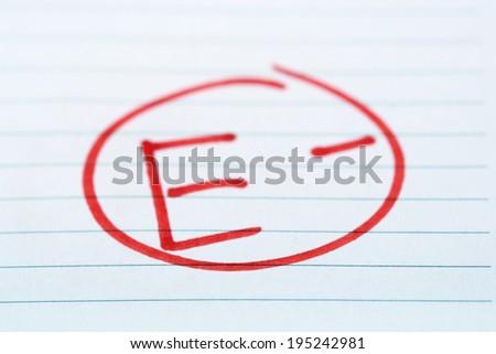 Grade E- written on an exam paper