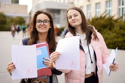 Grade / test results. Female students showing papers with perfect test result grade A, excellent mark for examination