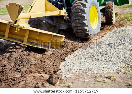 Grader digging a ditch for draining on a gravel driveway