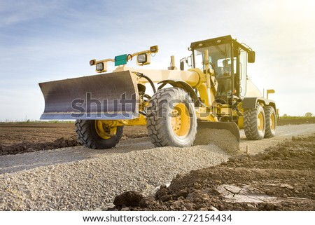 Grader leveling gravel on road construction site