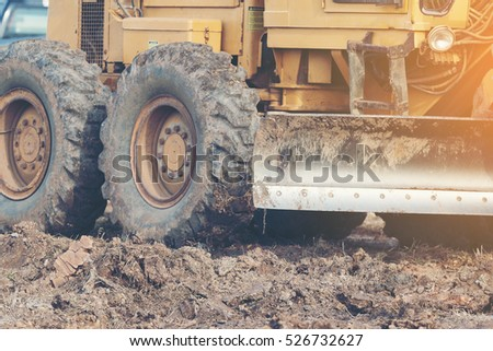 Grader leveling landfill on construction site before kick off project