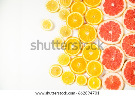 Gradient colors citrus slices - grapefruit, orange and lemon, placed on white background from left to right, from big to smaller sizes