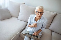 Gradual process.Beautiful mature woman touching shirt and having hot flash. Exhausted mature woman entering menopause. Portrait of an attractive senior woman sitting on a sofa at home with a hot flash