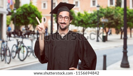 graduate bearded man with a proud, happy and confident expression; smiling and showing off success while gesturing victory with both hands, giving an