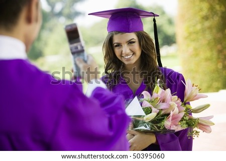 Graduate Having Picture Taken with Cell Phone outside