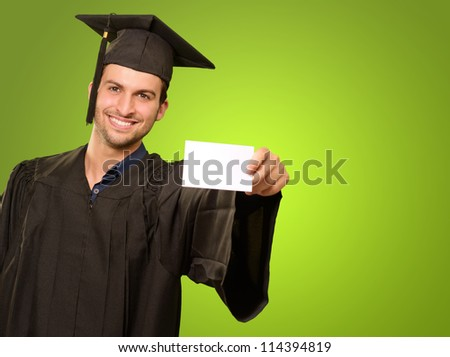 Graduate Man Holding Blank Card On Green Background - stock photo