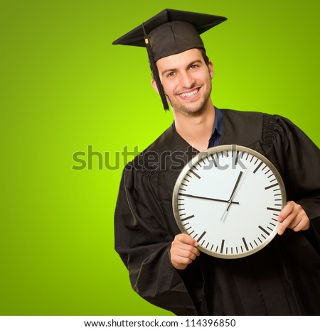Graduate Man Holding Clock On Green Background