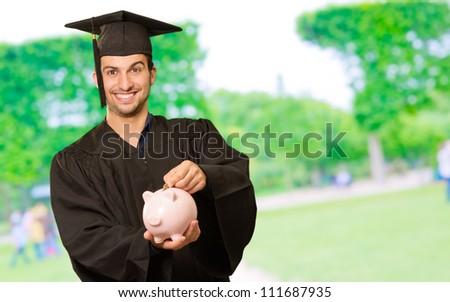Graduate Man Holding Piggy bank In Park