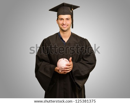 Graduate Man Holding Piggy bank Isolated On Grey Background