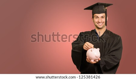 Graduate Man Inserting Coin In Piggy bank On Coloured Background