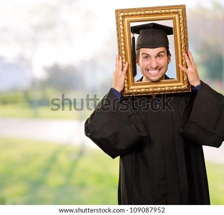 Graduate man looking through a frame, outdoor