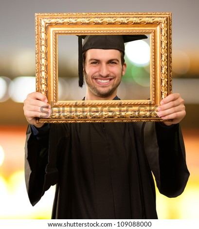Graduate man looking through a frame, outdoor - stock photo