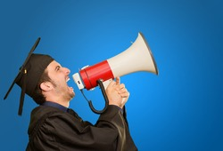 Graduate Man Shouting Into The Megaphone On Blue Background
