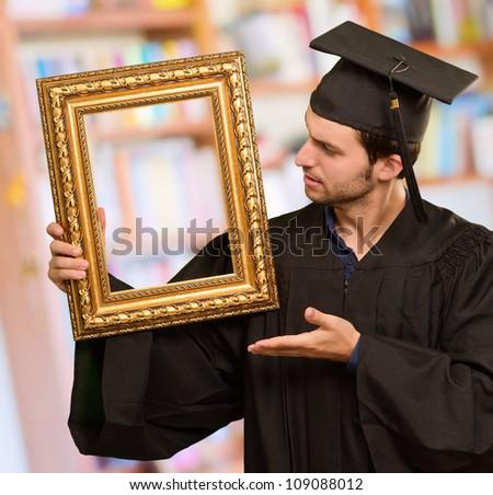 Graduate man showing a frame, indoor