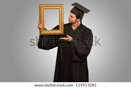 Graduate man showing a frame isolated on grey background