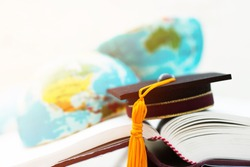 Graduate or Education knowledge learning study abroad concept : Graduation cap on opening textbook with blur of america australia earth world globe model map in Library room of campus, Back to School