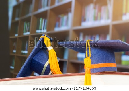 Graduate or Education knowledge learning study abroad concept : Graduation cap on opening textbook in old library stack of text literature on table with bookshelves in university college, light flare #1179104863