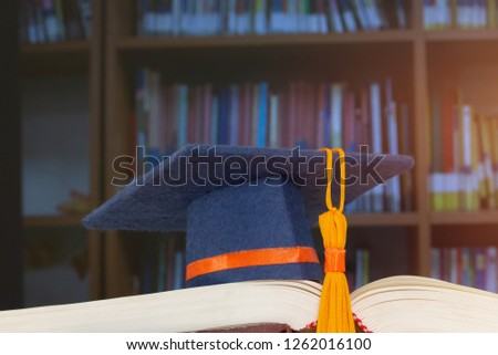 Graduate or Education knowledge learning study abroad concept : Graduation cap on opening textbook in old library stack of text literature on table with bookshelves in university college, light flare #1262016100