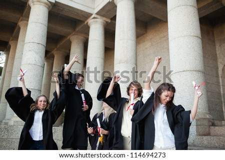 Graduates dancing in togas in front of their university - stock photo