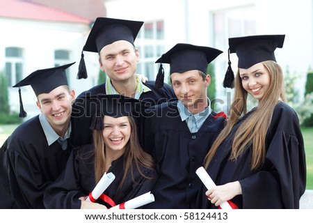 Graduates embrace, enjoy and look at the camera