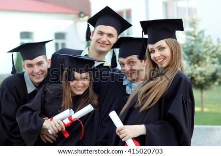 Graduates embrace, enjoy and look at the camera on the graduation ceremony. Happy graduation day. 5 graduates hold his graduate diplomas in their hands. #415020703