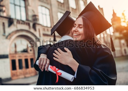 Graduates in mantles with diplomas in hands are standing near university and hugging each other.