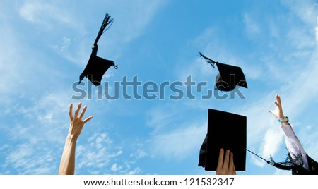graduates throwing graduation hats in the air.