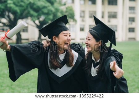 Graduation asian female friends hold diploma. cheerful ladies students hugging shoulders arms with thumb up finger hand gesture best sign. beautiful cheerful women students looking each other smiling