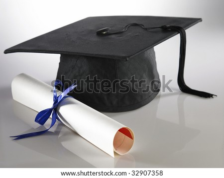 Graduation cap and diploma on the plain background