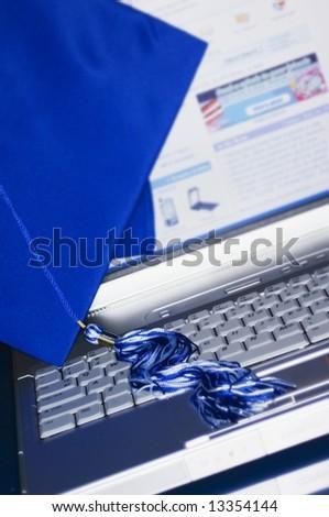 Graduation cap and tassel setting on laptop computer