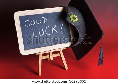 """Graduation cap hanging on a blackboard with """"good luck"""""""