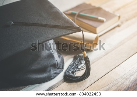 graduation cap, hat with degree paper on wood table graduation concept.