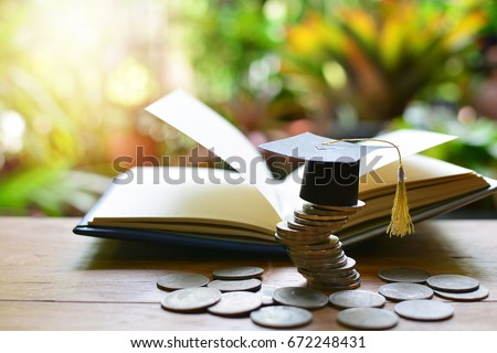 Graduation cap on saving coins for concept finance and education scholarships