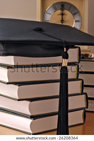 Graduation cap on stack of books with clock in background.  Softly lit still life with shallow dof.