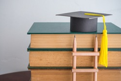 Graduation cap on textbooks with pencil ladder in classroom background copy space. Business education, abroad educational and goal or target successful graduation concept.