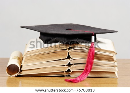 Graduation cap with book and diploma