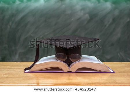 Graduation cap with glasses over the Books on the desk in class room with black board background,Education concept