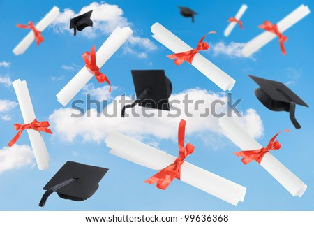 Graduation caps and diploma scrolls against a blue sky
