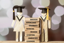 Graduation celebrating cap People Sign wood with on wooden square blocks tower blur bokeh. spelled out letter e.g education, graduate, learn. Ideas for international Educational Back to School Concept