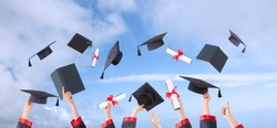 graduation ceremony hands and hats up with sky background