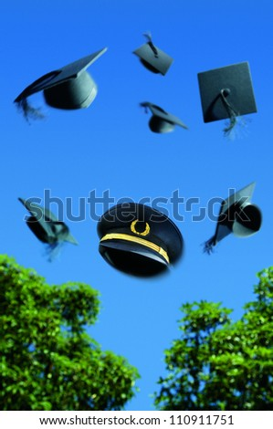 Graduation ceremony with Mortar boards thrown into the air with a pilots hat in the middle.
