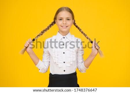 Graduation concept. Primary education. Perfect schoolgirl. Welcome back to school. Small schoolgirl with happy smile. Little schoolgirl looking nice in school uniform. Cute schoolgirl with long hair.