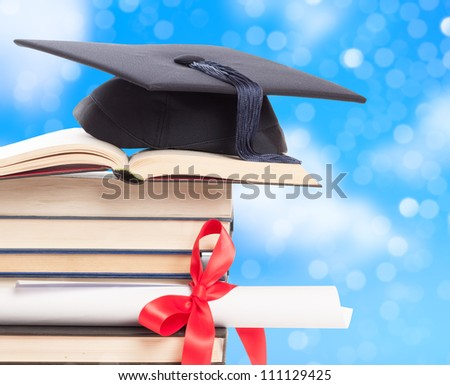 Graduation concept with mortar board and diploma against a blue background