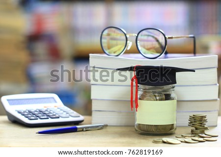 Graduation hat on the glass bottle on bookshelf in the library room background, Saving money for education concept #762819169