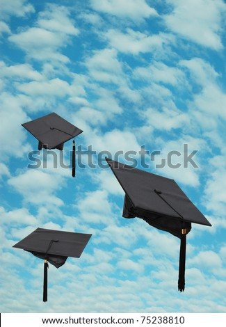 Graduation hats on natural cloudy sky