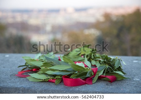 Graduation laurel wreath with red ribbon laying on a granite slab with a view to Rome city (out of focus) #562404733